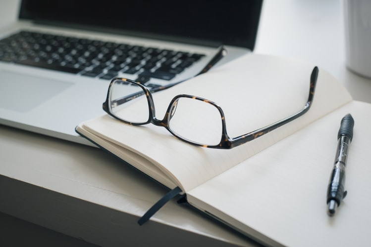 Pair of Glasses, Notebook, Pen and Laptop on a Desk